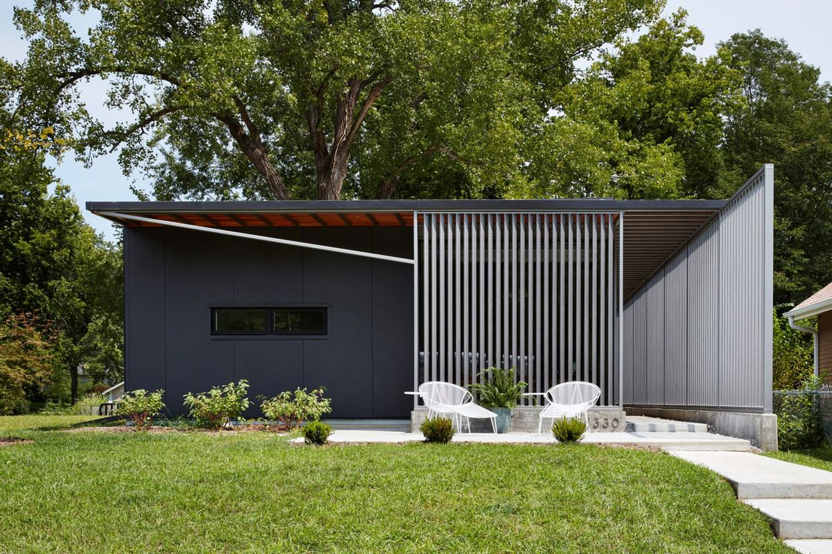 Exterior shot of flat-roofed home with dark grey paneled walls and a steel screen on one half of the front and running along the side, with a manicured front lawn and concrete steps leading up to entrance.
