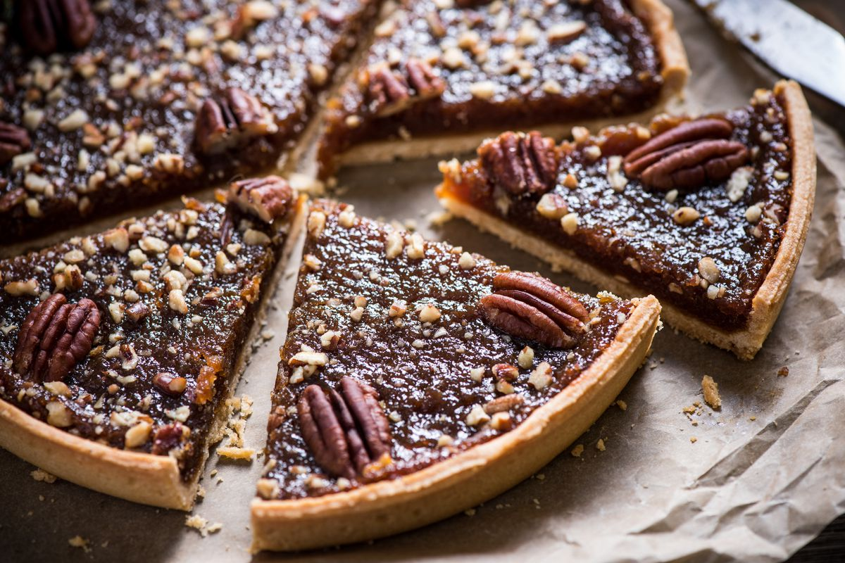 Slicing a pecan tart on a wooden table from an overhead view.
