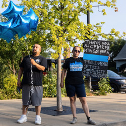 Supporters hold balloons and a sign during a memorial and prayer service for fallen Officer Ella French outside the 22nd District Police Station Wednesday.