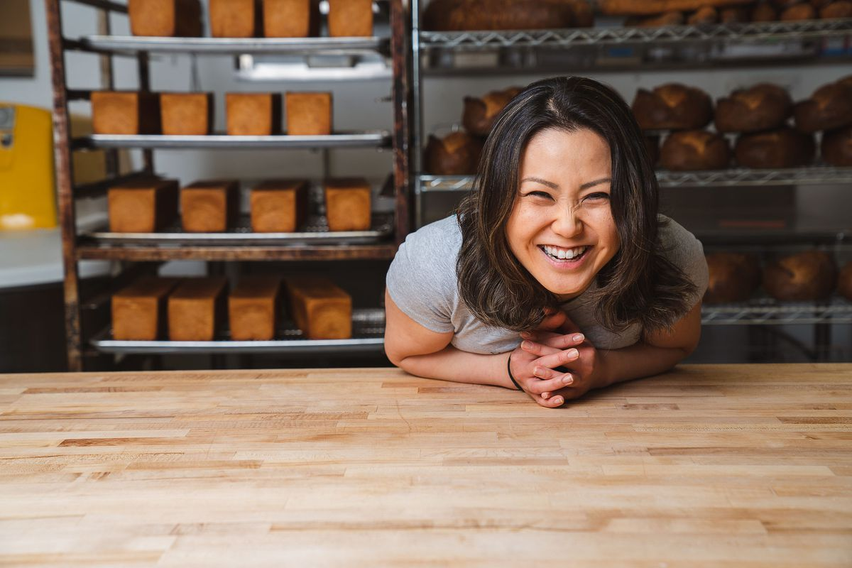 An Asian-American woman smiles and leans over a wooden table.