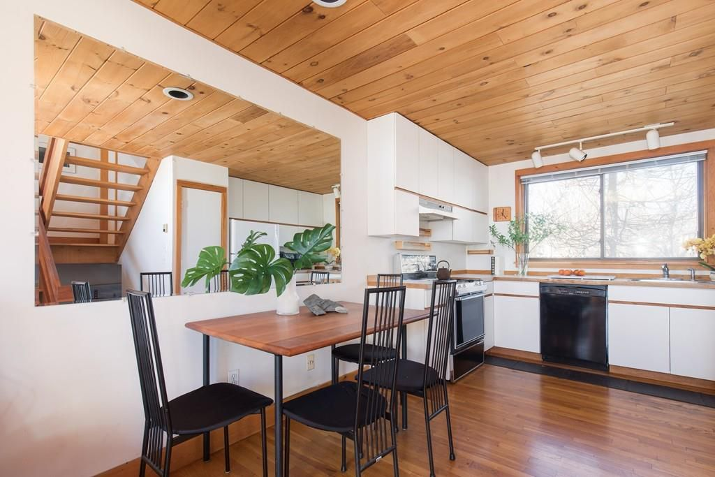 An open kitchen with an L-shaped counter and a table and chairs.