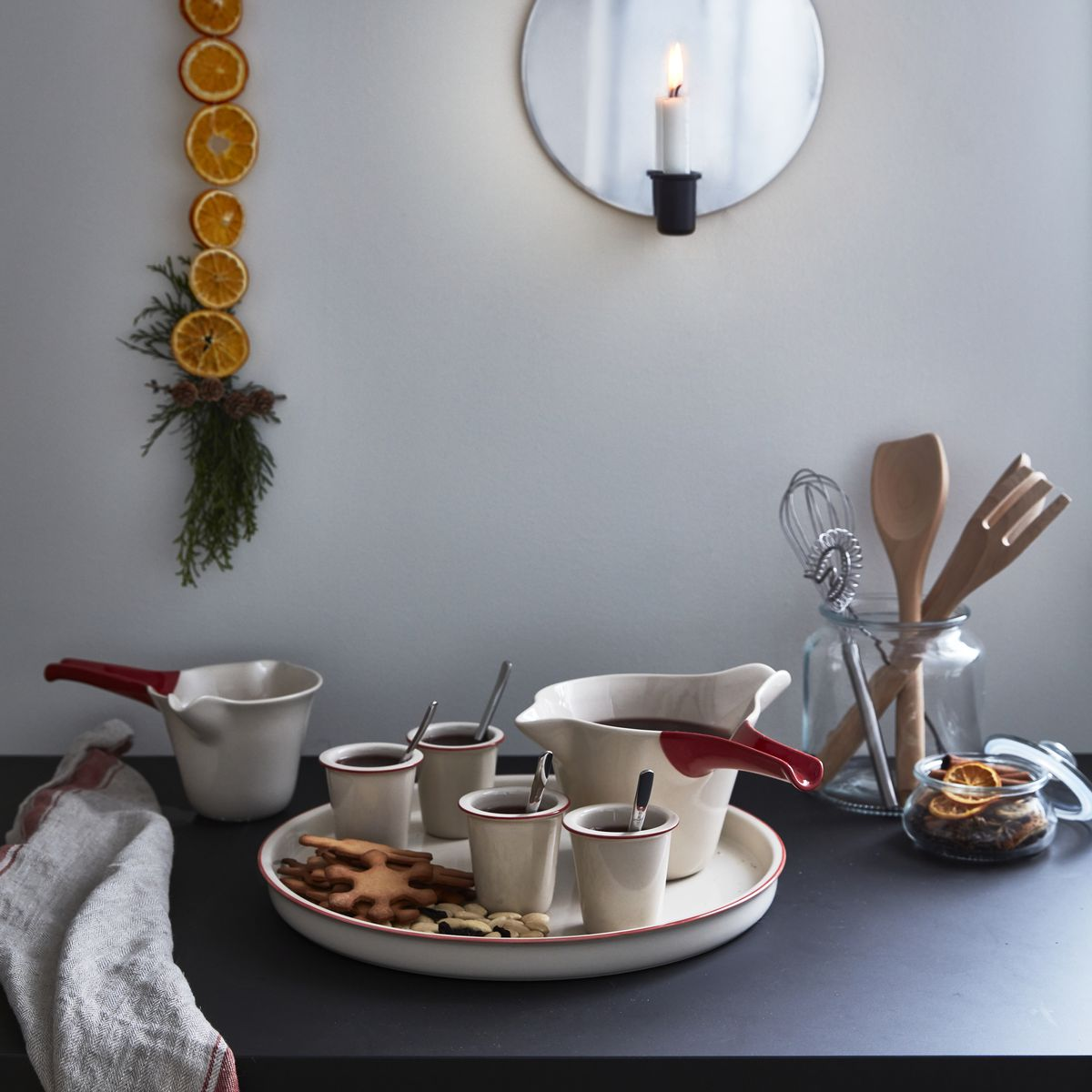 On a table sits various serveware, including a tray with cookies and mugs, and a jar with cooking utensils. A round mirror on the wall has a built-in candle holder in the front.