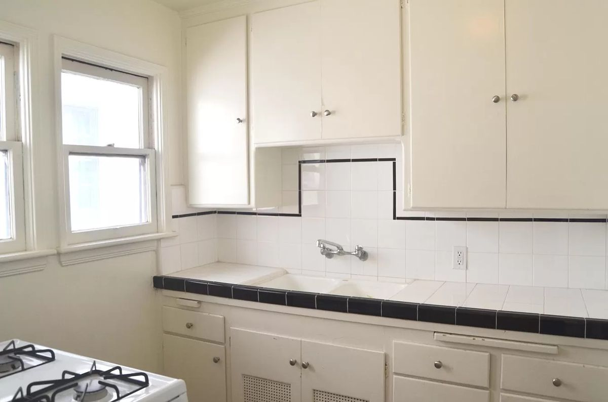A kitchen with tile countertops and an older gas stove