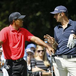 Tiger Woods, left, listens to Dustin Johnson at the tee box of the second hole during the final round of the BMW Championship PGA golf tournament at Crooked Stick Golf Club in Carmel, Ind., Sunday, Sept. 9, 2012.