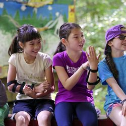 Girl Scouts Ket Davis, left, Em Kong, Lily Pogue and Rowan Rhoads laugh as they try to figure out a hand signal at a Girl Scout day camp. | AP Photo