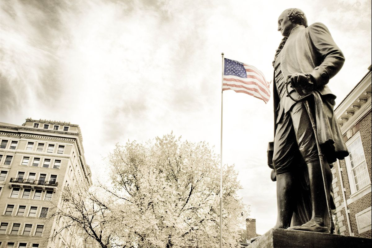 A statue of George Washington with the American flag in the background in front of Independence Hall.