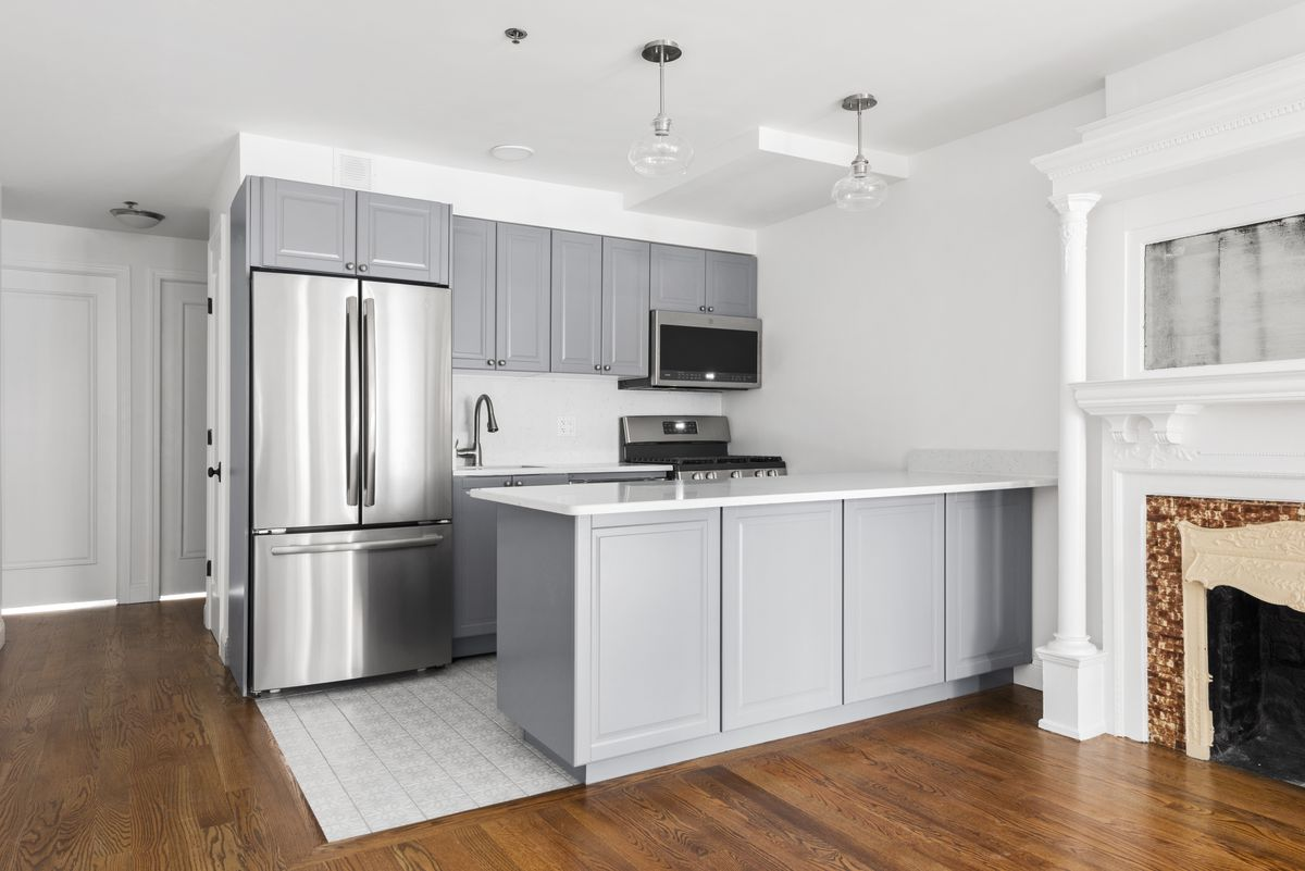 A kitchen with grey cabinetry, hardwood floors, and an island.