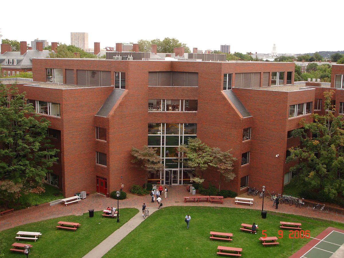 A five-story academic building with a courtyard in front of it.