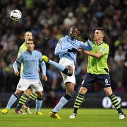 Manchester City's Mario Balotelli, centre, and Aston Villa's Ciaran Clark, right battle for the ball during their English League Cup third round match at the Etihad Stadium in Manchester, England, Tuesday Sept. 25, 2012.