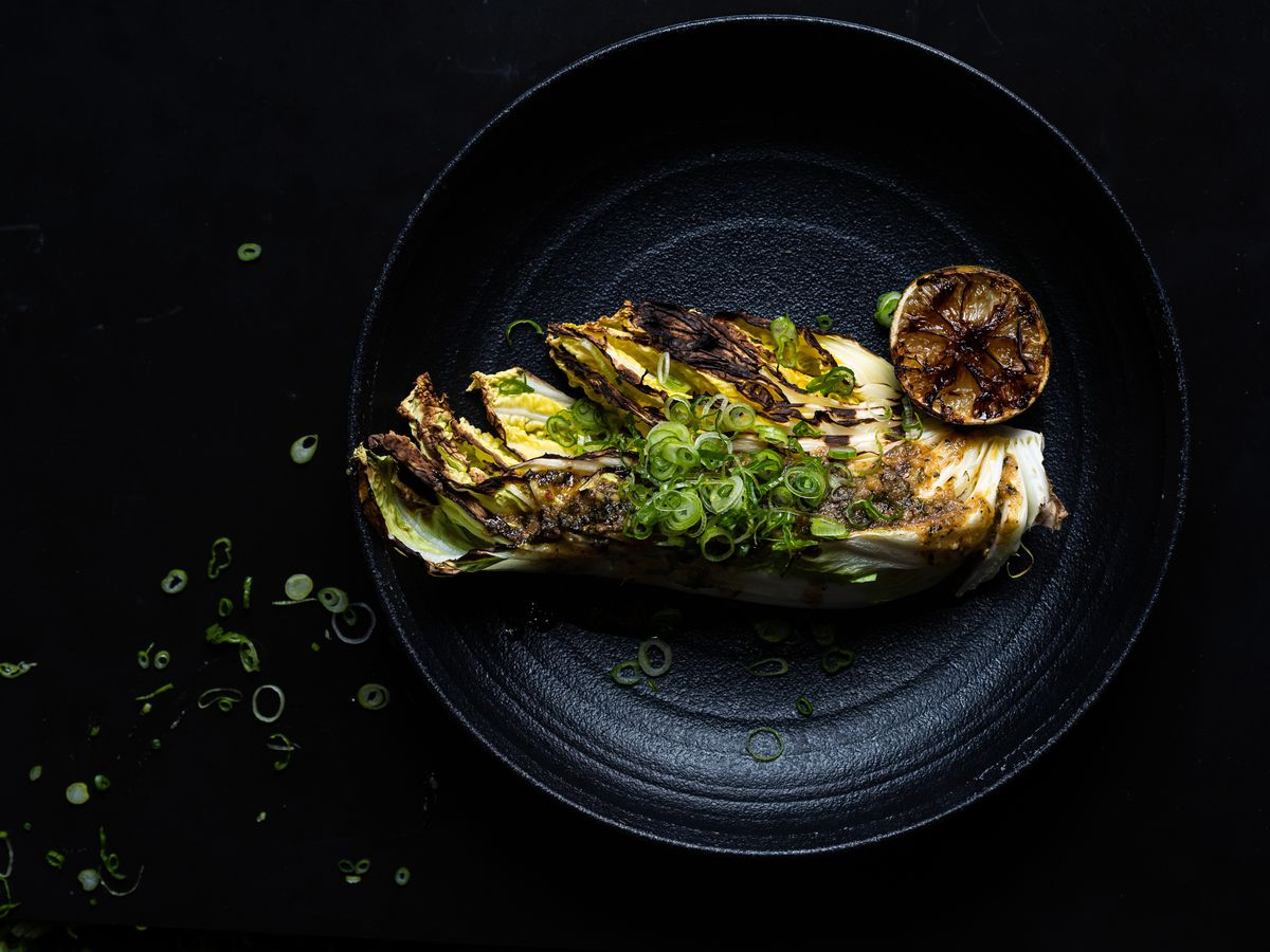 A wedge of charred cabbage in brown butter miso with a charred lime.