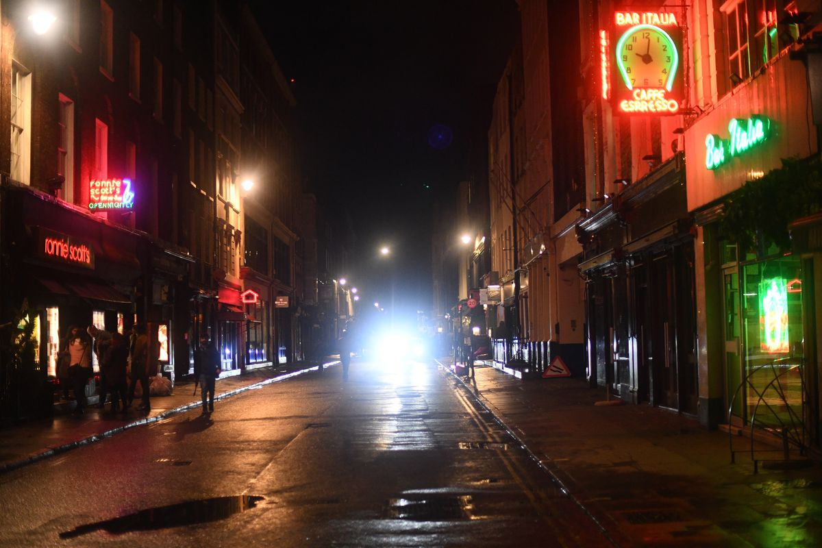 An empty street in Soho at 10:06p.m., with taxi headlights in the distance