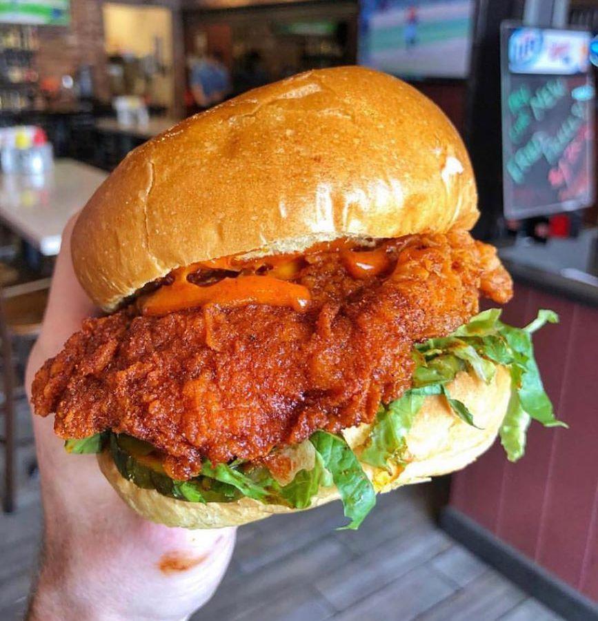 Hand holding Nashville hot chicken sandwich