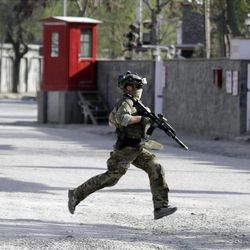 A NATO soldier runs to the scene of a attack by Taliban militants in Kabul, Afghanistan, Sunday, April 15, 2012. The Taliban launched a series of coordinated attacks on at least seven sites across the Afghan capital on Sunday, targeting NATO headquarters, the parliament and diplomatic residences. Militants also launched near-simultaneous assaults in three other eastern cities. (AP Photo/Ahmad Jamshid)