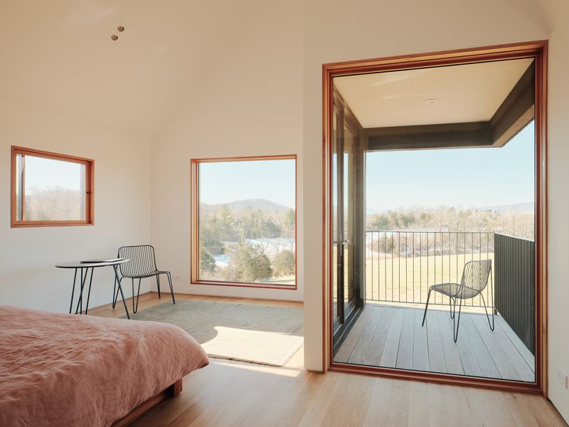 Bedroom with two large windows and a small terrace.