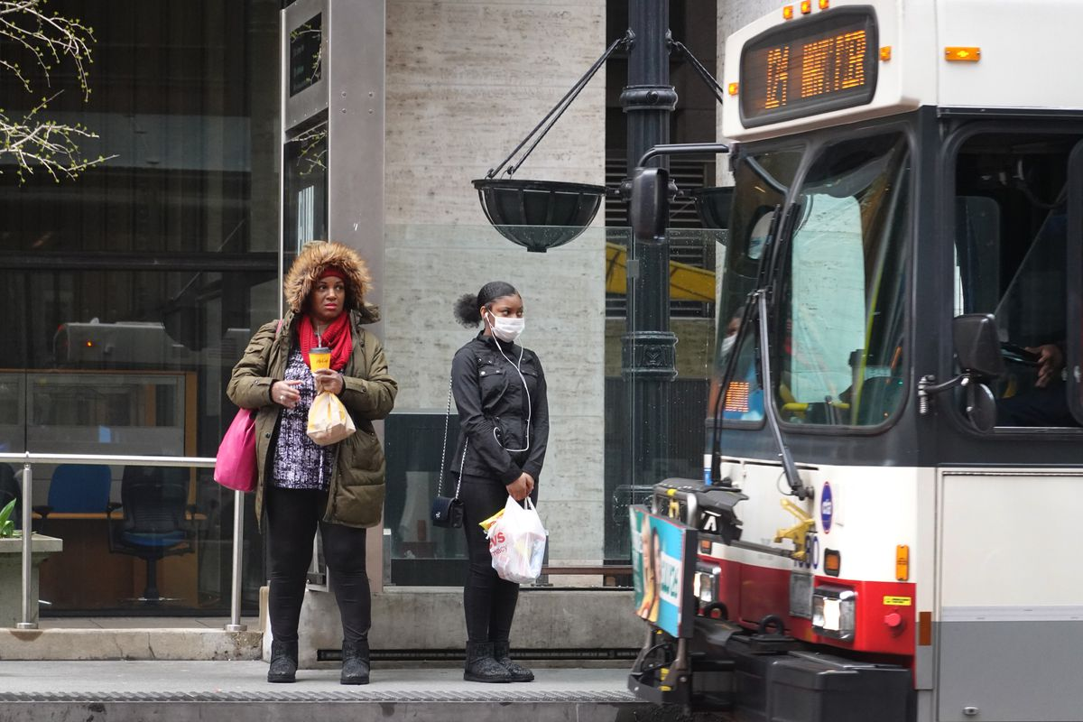 Two riders stand waiting to board a bus on the loop in Chicago.