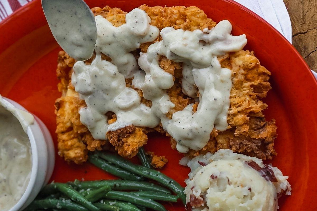 Gravy-covered fried chicken and sides from Red's Porch