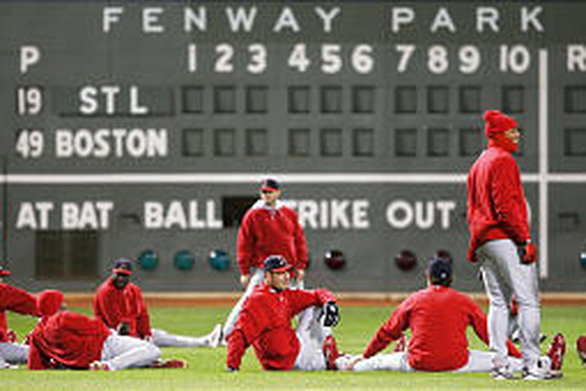 """St. Louis players stretch out in front of the """"Green Monster"""" wall at Fenway Park in Boston in preparation for Game 1 of the World Series."""