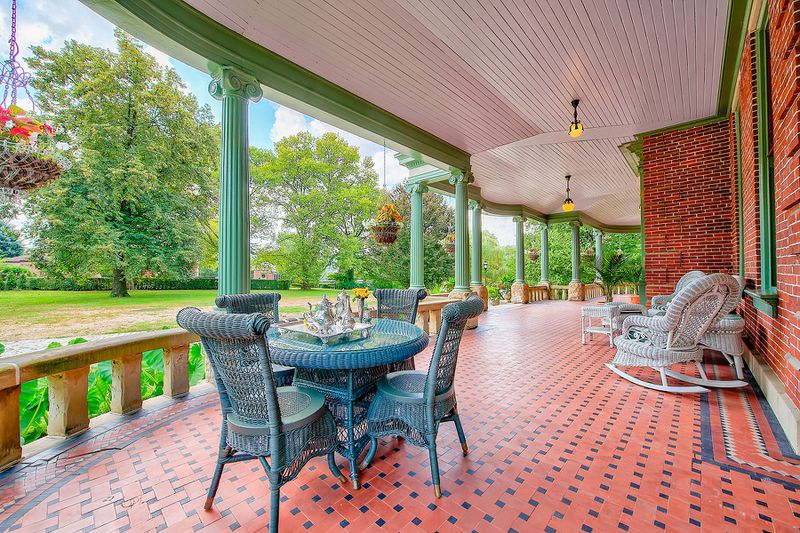A large patio has red and blue checkered tile, green columns, and a navy wicker outdoor dining set.