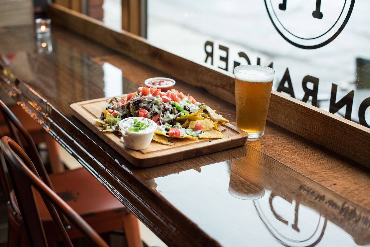 Facing the Iron Ranger's front window is a cutting board loaded with nachos next to a pint of beer