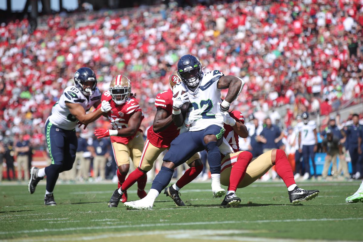 Fred Warner #54 of the San Francisco 49ers tackles Chris Carson #32 of the Seattle Seahawks for a loss at Levi's Stadium on October 3, 2021 in Santa Clara, California.