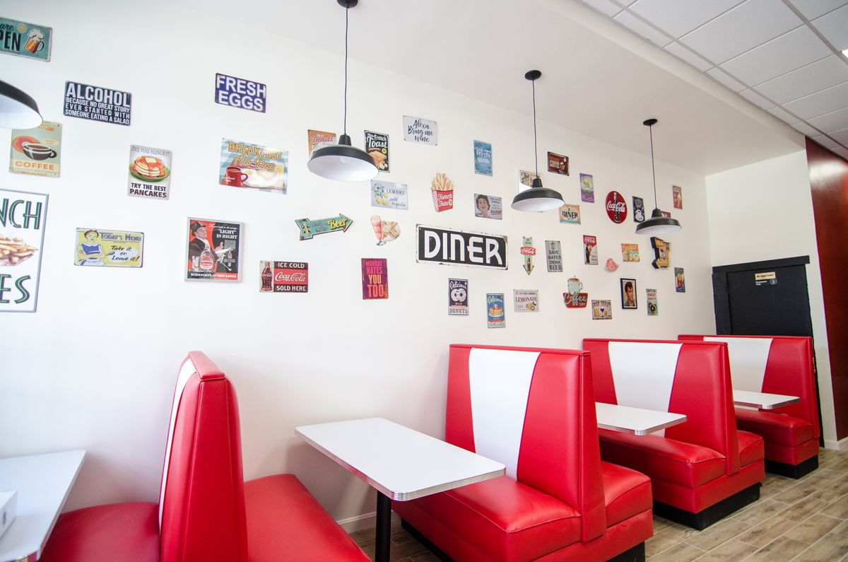 Retro-style bright red and white booths line a restaurant wall, which is decorated with a bunch of vintage diner signs