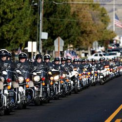 The funeral procession for North Salt Lake Police Officer Charles Skinner heads to Bountiful City Cemetery Friday.