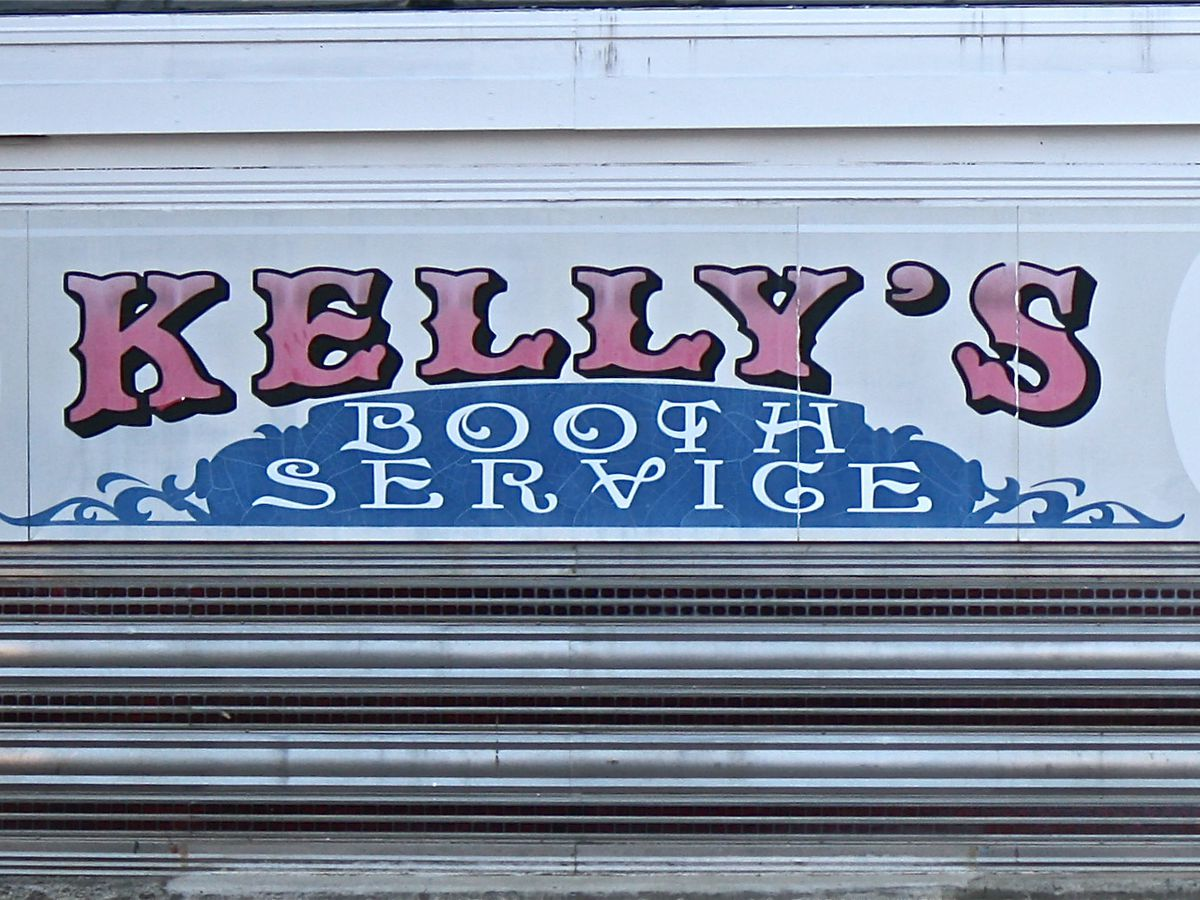 """Closeup of signage at an old-fashioned diner. It reads """"Kelly's Diner"""" and """"booth service."""""""