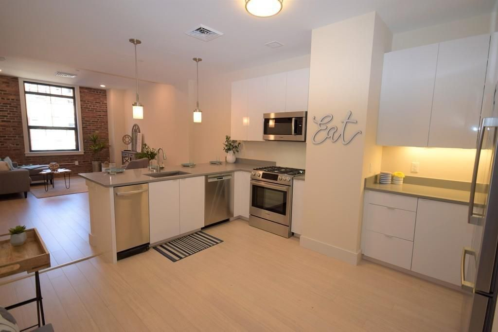 An open kitchen with a counter separating it from the living room area.