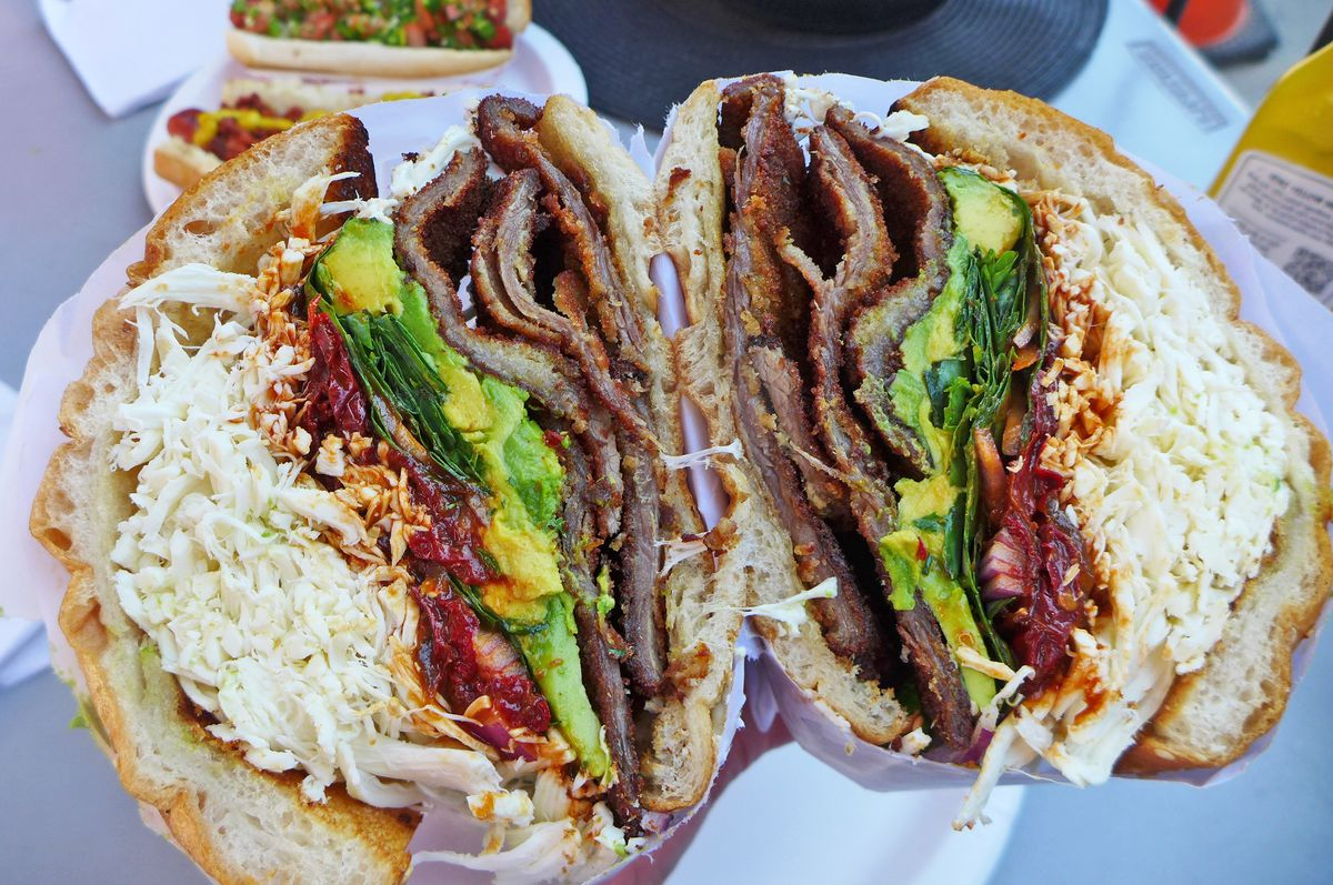A giant round sandwich split in half shown in double cross section, cheese and meat bursting out.