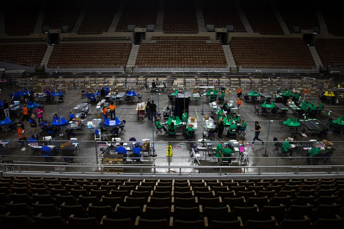 Contractors sitting at a number of tables in a large arena examine Maricopa County ballots from the 2020 election.