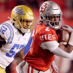 Utah Utes running back Zack Moss (2) outruns UCLA Bruins linebacker Lokeni Toailoa (52) on a play as Utah and UCLA play a college football game in Salt Lake City at Rice-Eccles Stadium on Saturday, Nov. 16, 2019.