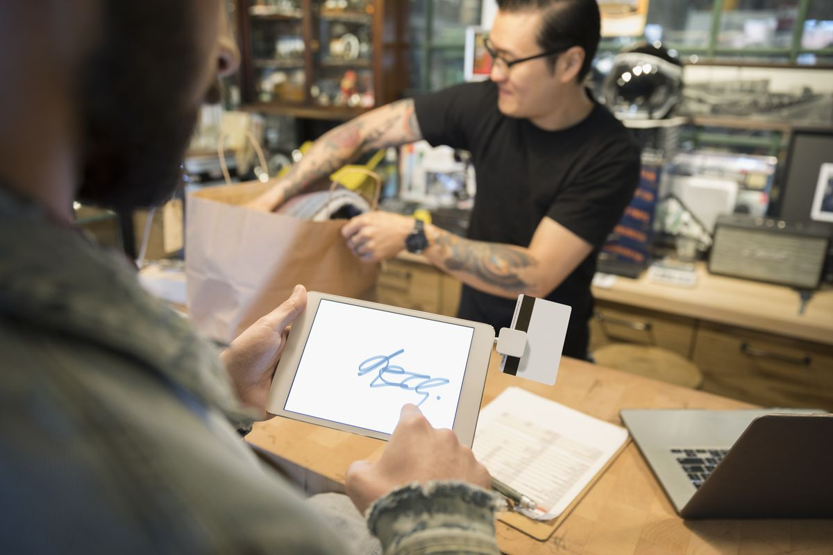 A man illegibly signing a receipt on a tablet at a motorcycle shop