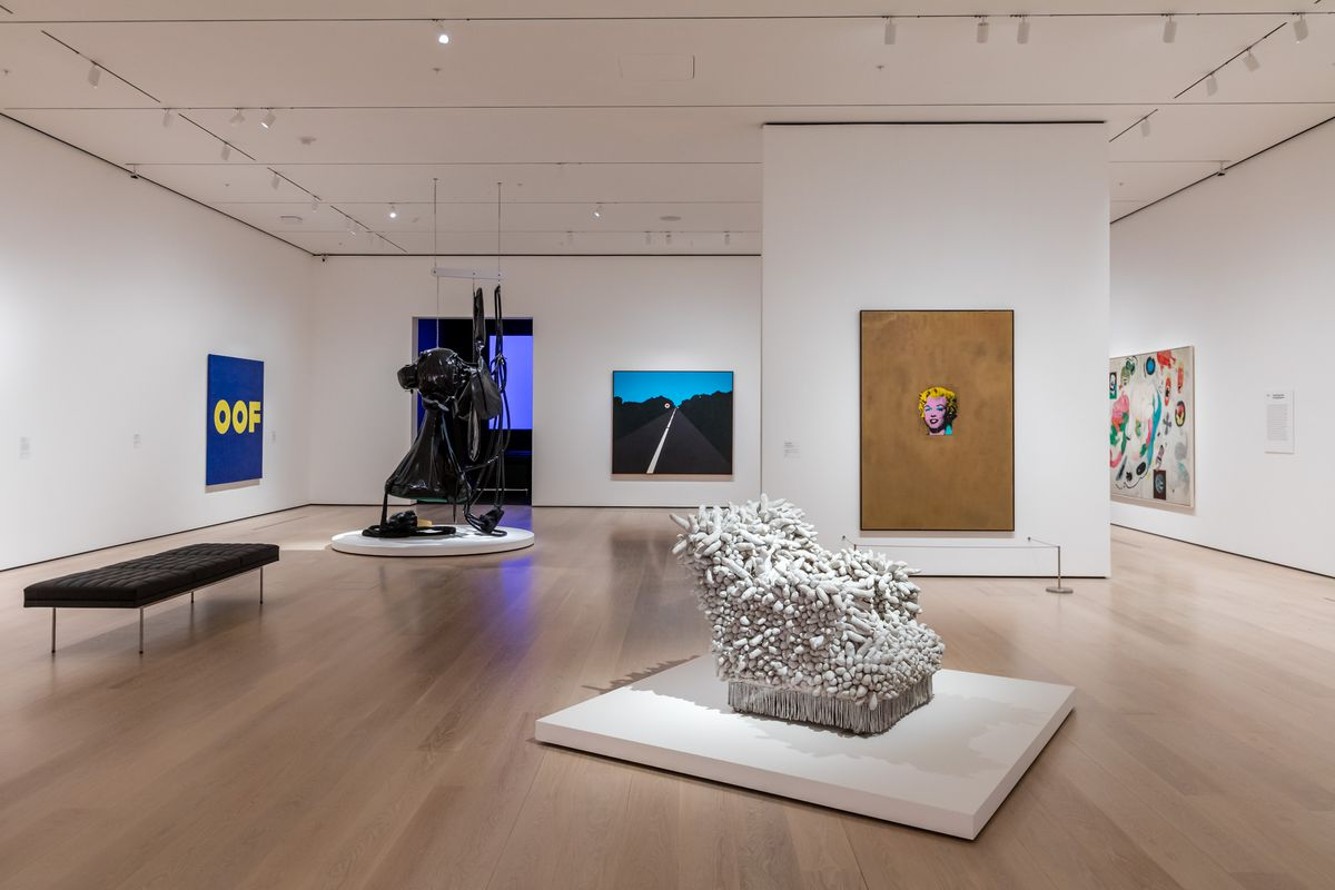 A gallery with a black sculpture piece and white sculpture piece, with colorful artworks on the walls.