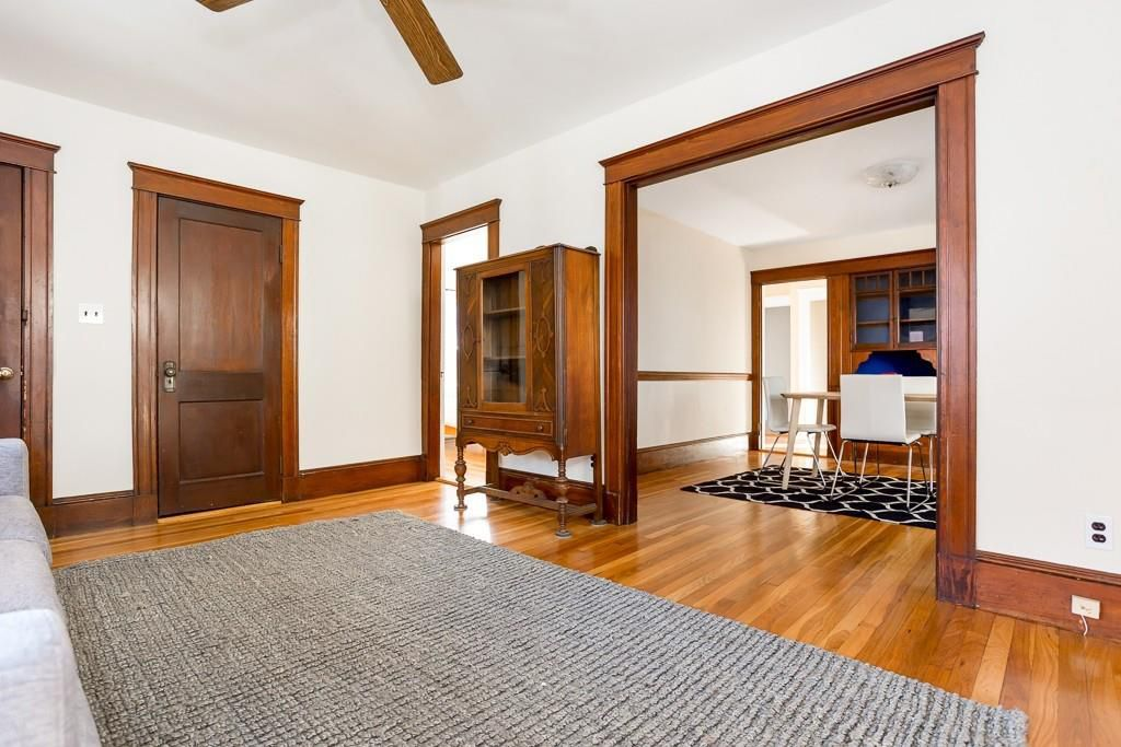 A largely empty living room and dining room separated by a large entry way.