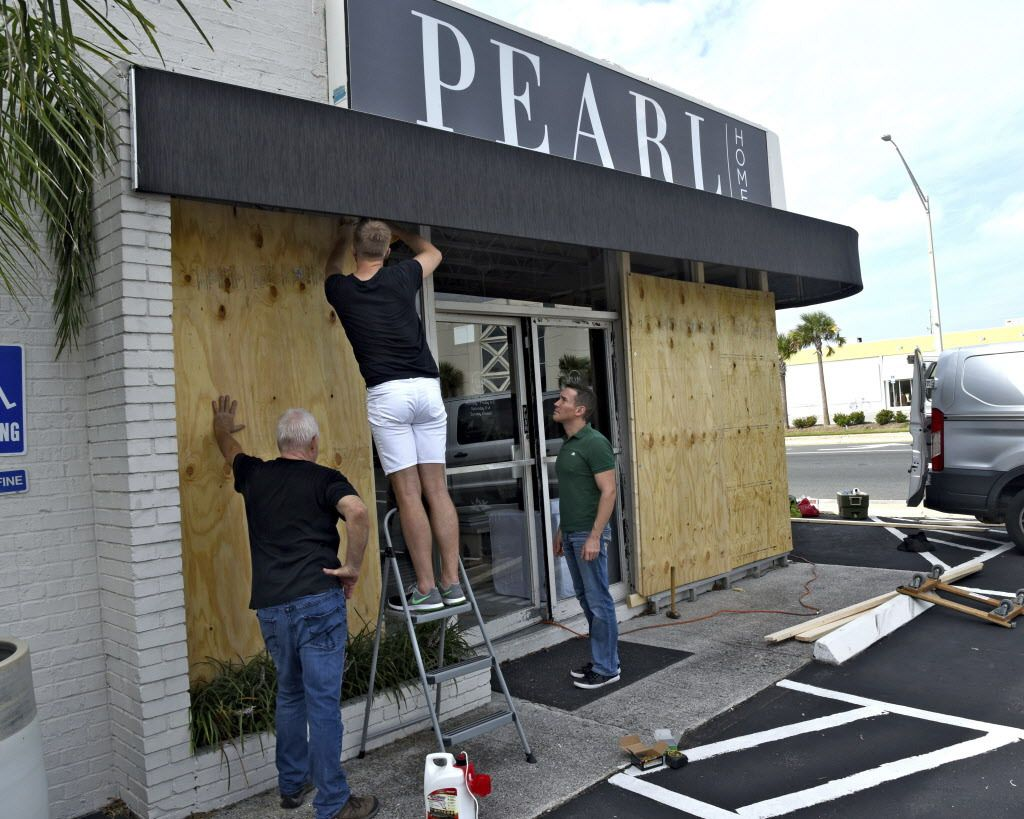 Employees Ron Weible (left), Casey Shroyer and David Tibbs, of the Pearl Home store, board up the windows of the business in advance of Hurricane Irma, on Thursday Sept. 7, 2017, in Jacksonville Beach, Florida. | Bob Mack/The Florida Times-Union via AP