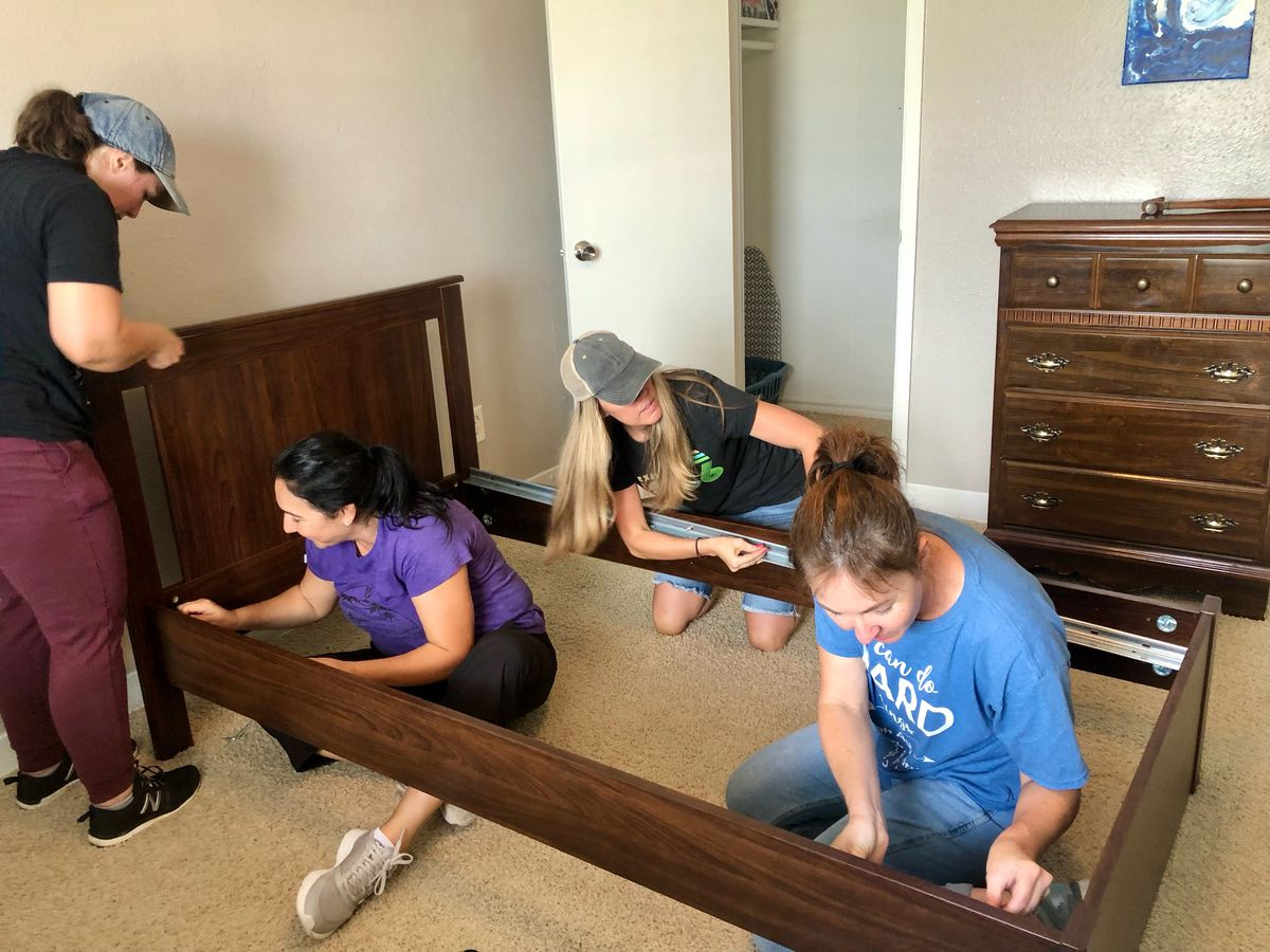 Volunteers assemble a bed as part of an on-going service project to furnish apartments for incoming refugee families in Houston.