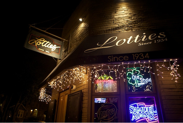 """An awning outside a brick bar reads """"Lottie's Since 1934"""""""
