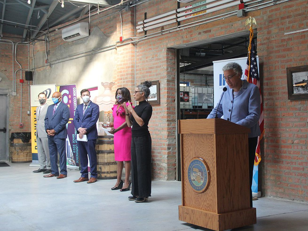 Cook County Commissioner Kevin Morrison, third from left, looks on while Cook County Board President Toni Preckwinkle speaks at Thornton Distilling Company Sept. 23.