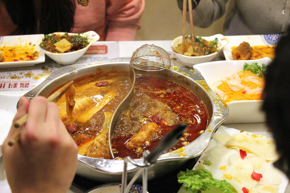 A hand lifts food from a silver hot pot bowl with a divider in the middle.