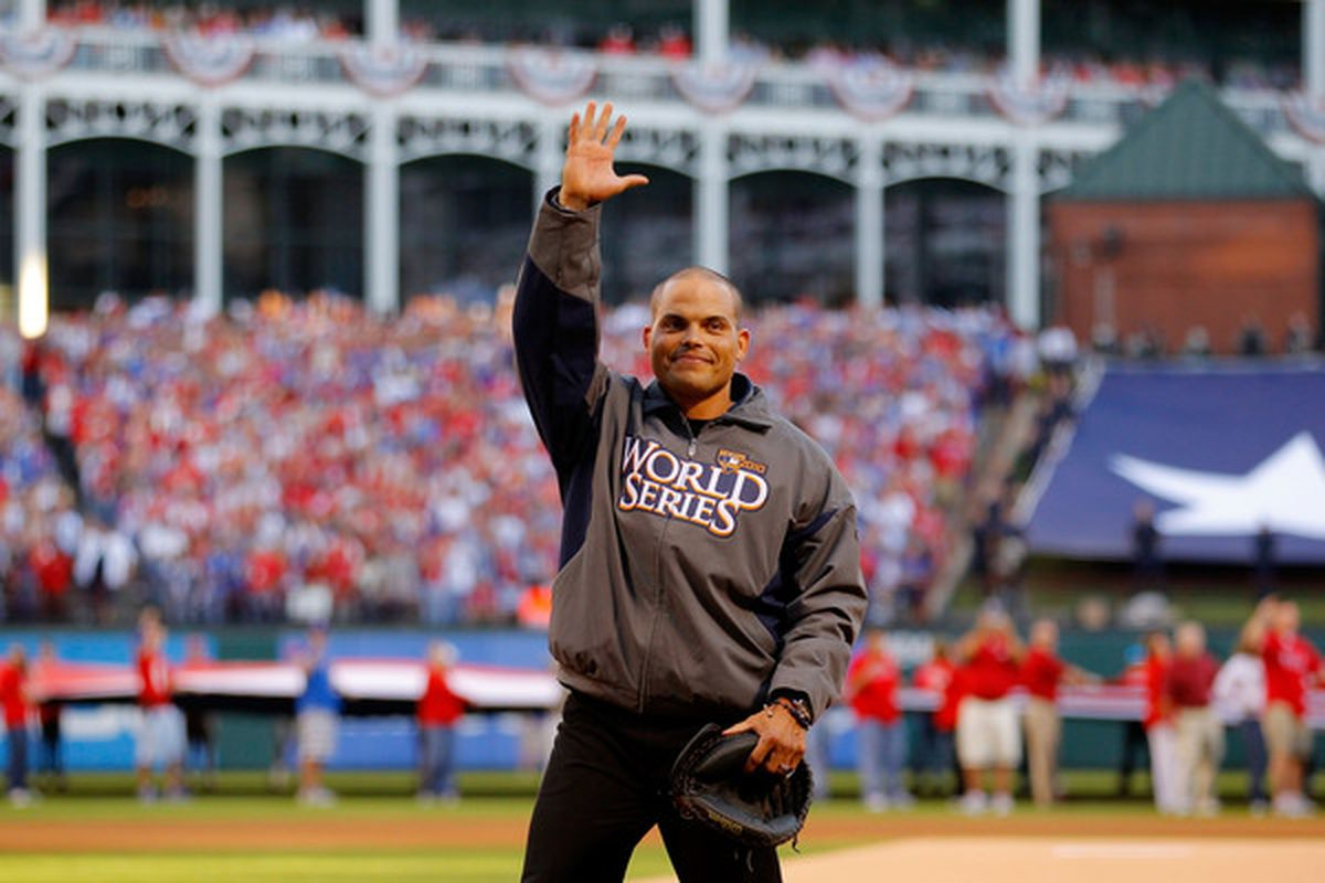"""Former catcher for the Texas Rangers Ivan """"Pudge"""" Rodriguez waves to the fans as he walks out to catch the ceremonial first pitch from Rangers team President Nolan Ryan. (Photo by Brian Snyder-Pool/Getty Images)"""