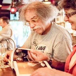 Longtime bartender Tony Lioce, left, and regular Marilyn Saner, right, looking at a book celebrating the bar.