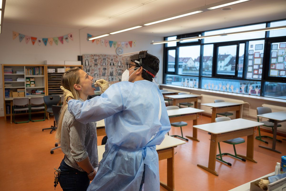 A doctor swabs a teacher's throat in an elementary school classroom before pupils arrive.