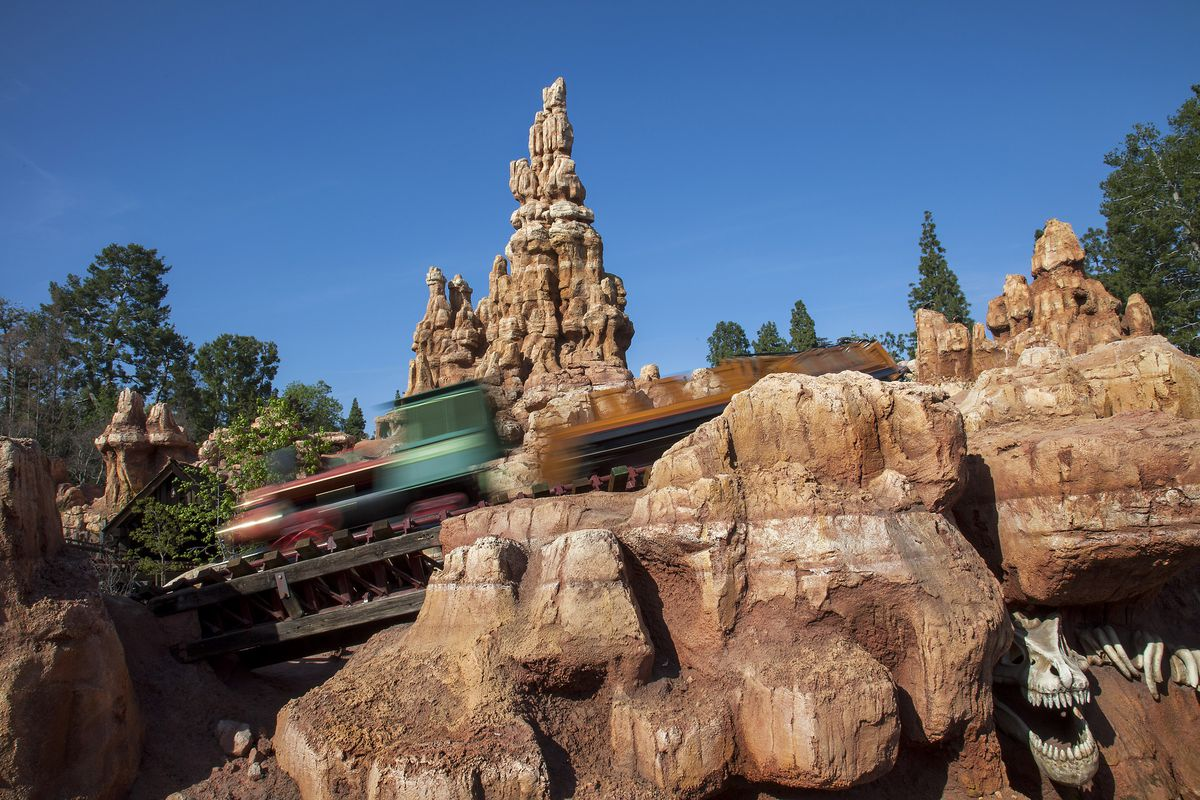 A train zips through Big Thunder Mountain and past the historic Rainbow Ridge Mining Town. Big Thunder Mountain Railroad, a popular roller coaster attraction, is located in Frontierland at Disneyland Park in Anaheim, Calif. For editorial news use only.
