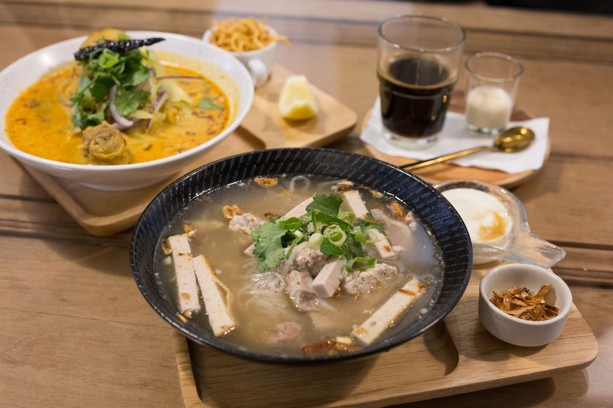 A table with a bowl of curry, a bowl of duck noodle soup, and smaller bowls with sauces and seasonings