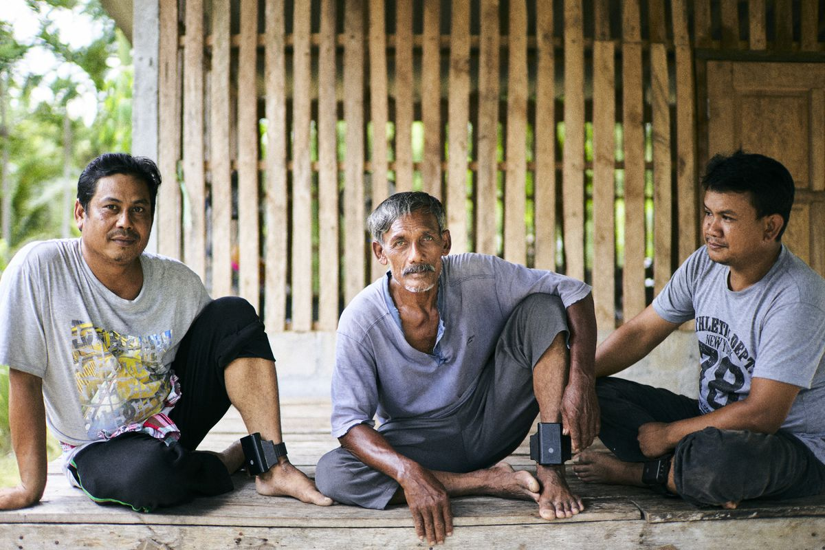 Three men crouch with visible ankle braclets