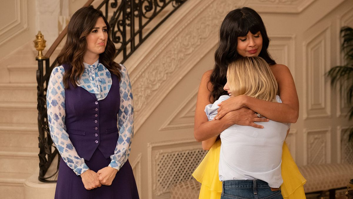 """Eleanor (Kristen Bell) and Tahani (Jameela Jamil) hug as Janet (D'Arcy Carden) looks on sadly in a screenshot from The Good Place season 4, episode 13, """"Whenever You're Ready"""""""