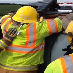 """Emergency responders work to extract a woman from a damaged car. Rev. Patrick Dowling revealed himself as the mysterious """"angel priest"""" who prayed with 19-year-old Katie Lentz, after reading a National Catholic Register article about the Missouri accident that occurred last week."""
