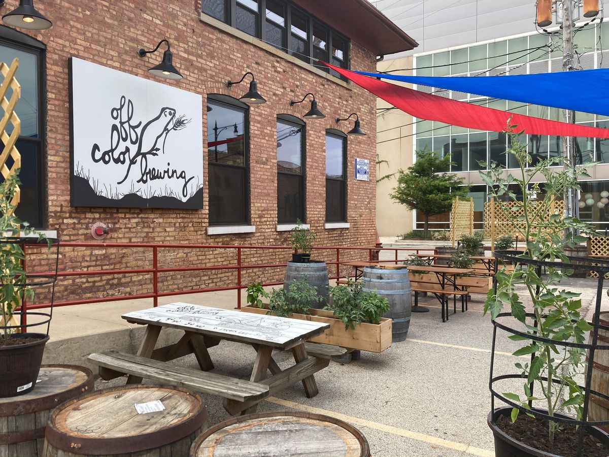 """A patio with wooden furniture outside a brick building with a sign that reads """"Off Color Brewing"""""""