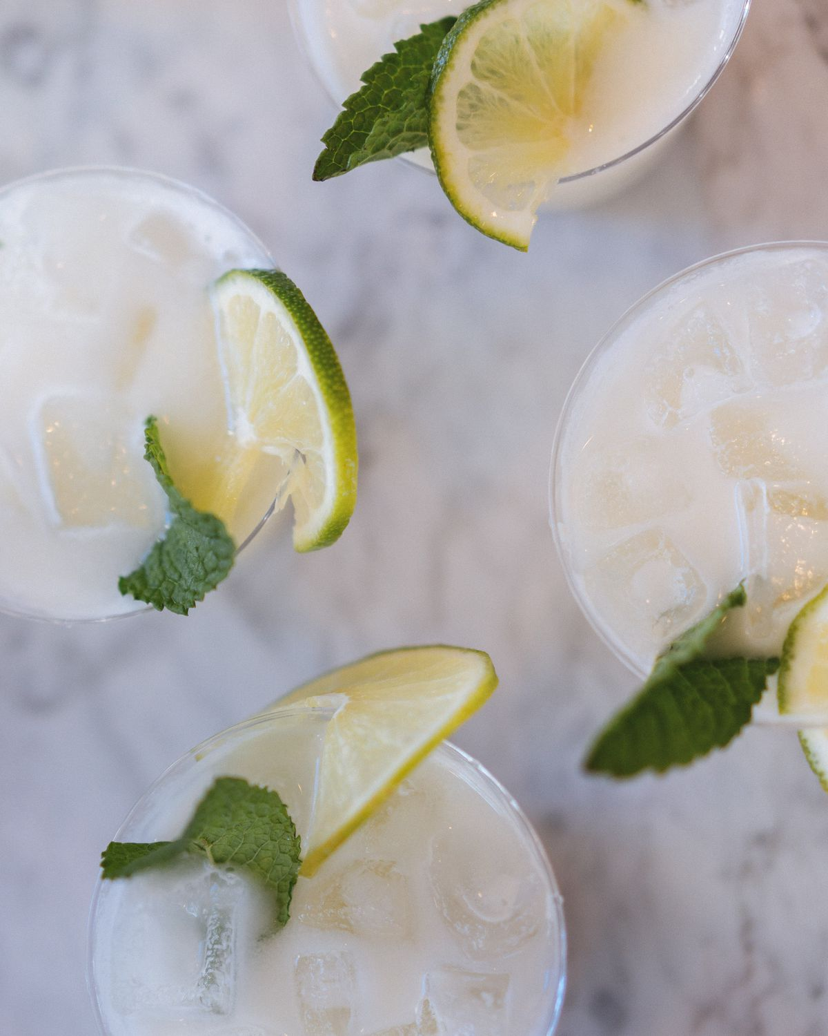 An overhead shot of four glasses of milky lime drink with a lime and mint.