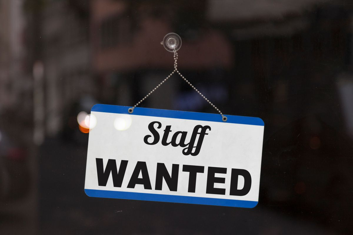 """A blue and white sign in a glass door reading """"staff wanted"""""""